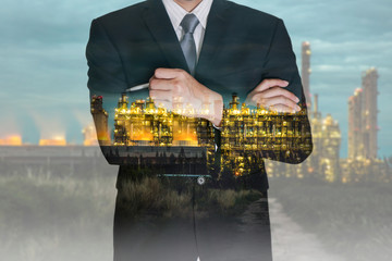 Double exposure of business man think idea and oil refinery industry plant, Electric Generating Factory in the night as Energy and Technology concept.