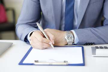 Portrait of businessman holding pen in his hand and signing the contract at business meeting.