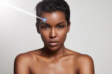 black woman's portrait closeup with a rey of laser on a face