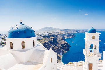Beautiful blue dome church and view of voclanic caldera in Imerovigli, village on Santorini island, Greece