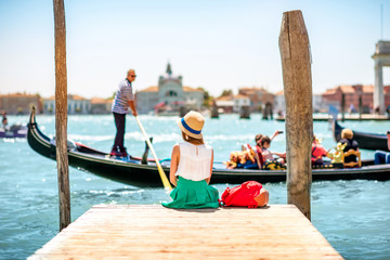 Poster Venice Young female traveler sitting on the pier and enjoying beautiful view on venetian chanal with gondolas floating in Venice