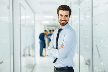 Young businessman is posing in hallway