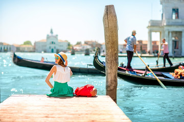 Türaufkleber Gondeln Young female traveler sitting on the pier and enjoying beautiful view on venetian chanal with gondolas floating in Venice