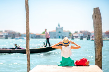 Autocollant pour porte Venise Young female traveler sitting on the pier and enjoying beautiful view on venetian chanal with gondolas floating in Venice