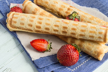 Wafer rolls with cream.   Wafer rolls with cream and fresh strawberries on a blue napkin on a light wooden background.