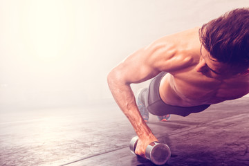 Man doing push-up exercise with dumbbell. Strong male doing crossfit workout.