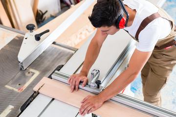 Tischler oder Schreiner schneidet Brett mit Stichsäge
