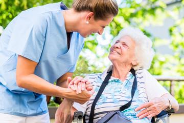 Altenpflegerin gibt Seniorin Glas Wasser zu trinken