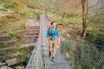 Hiker crossing suspension footbridge