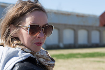 Woman in sunglasses with messy windswept short blonde hair