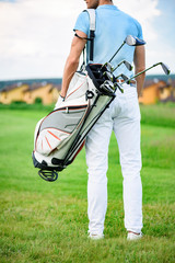 Young golfer holding golf bag