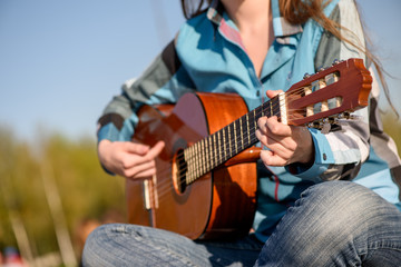 Close up shot without face. Woman playng guitar an the coast