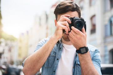 Pleasant cheerful man holding photo camera