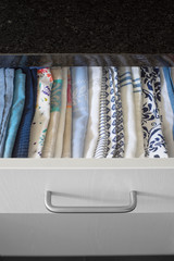 Tea towels smartly arranged in a drawer of kitchen cabinet. Selective focus.