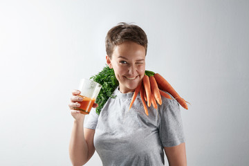 Young attractive girl with healthy perfect skin happily blinks on camera while drinking her fresh organic carrot juice with carrot harvest on her shoulders