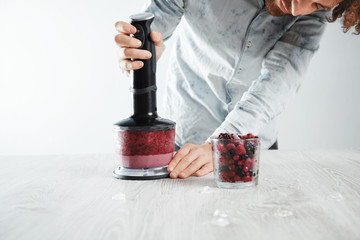 Bartender starts to blend frozen berries, ice, yougur and honey in blender to make healthy smoothie drink to refresh in summer time. Glass with frozen berries in front near