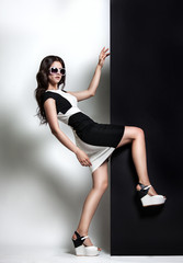 fashion portrait of a woman. young beautiful girl in black and white dress and sunglasses posing in the studio