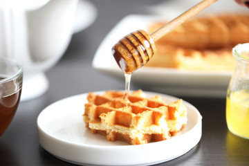 Tasty waffles with honey on plate