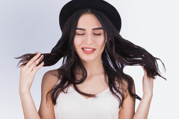 Gorgeous young woman in black hat playing with her hair on a gray background