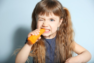 Little girl with carrot on wall background