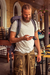 Handsome backpacker tourist with a beard using a mobile phone on the street