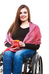 Woman invalid girl on wheelchair holds tea mug