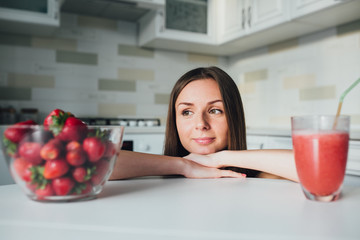Sports and sexy girl drinks strawberry smoothie in the kitchen