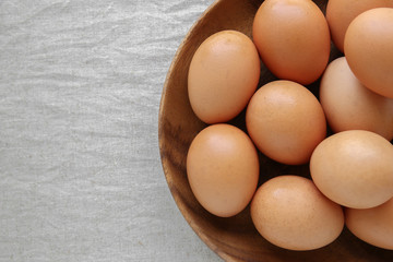 Eggs in wooden bowl on linen copy space background