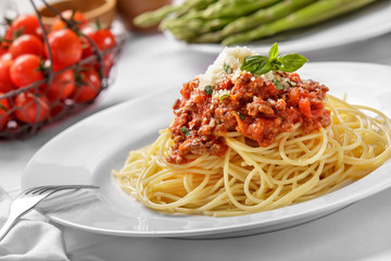 italian spaghetti bolognese topped with cheese and basil