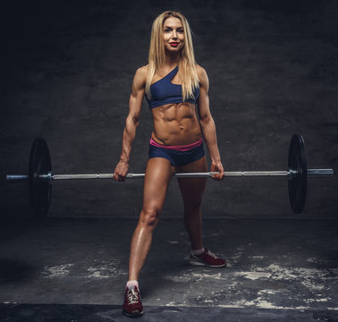 Female holding barbell between her legs.