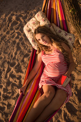 pregnant woman in hammock outdoor on the beach