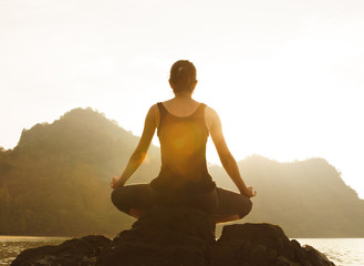 Silhouette of woman practicing yoga on the rock during a beautif