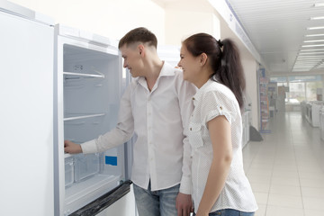 Happy family couple looking at large fridges in store