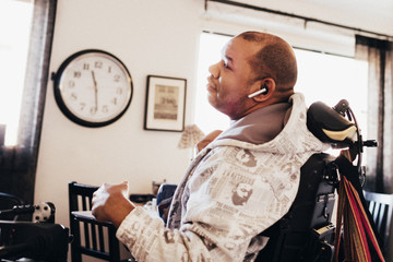Disabled musician on wheelchair in music studio