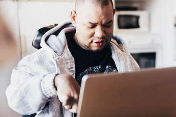 Disabled man using laptop in recording studio
