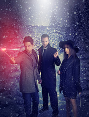 three young magicians holding a magic wand during a snowy night