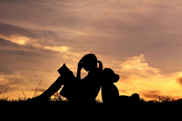 Silhouette a girl reading book with teddy bear on mountain and sky sunset