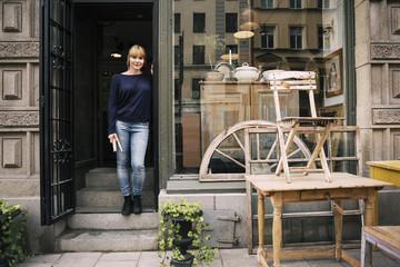 Female owner standing on entrance of antique shop