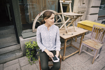 High angle view of woman with smart phone sitting on chair against store