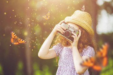 Little girl photographing butterfly