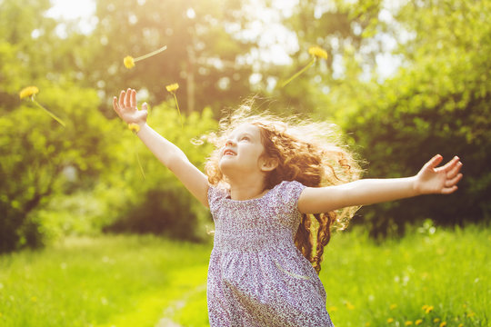 Child outstretched arms enjoying flying yellow dandelion