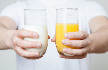 Male hands holding a glass of orange juice and a glass of milk
