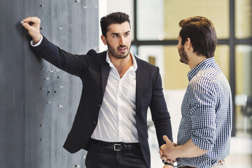 Young businessman pinning paper on notice board while talking with colleague in office