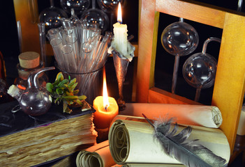 Two candles with magic bottles and vintage books