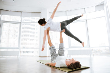 Pretty young woman practicing acro yoga with partner in studio