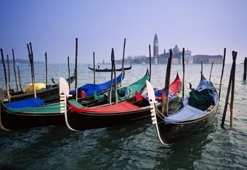 View past docked gondolas towards St.Mark's Square, from across the Grand Canal, Venice, Veneto, Italy