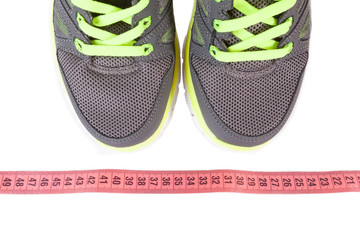 Sport shoes and pink measure tape isolated on white background.