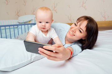 Mom and baby with the phone on the bed in the room.