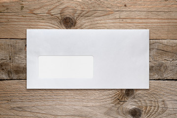 Blank envelope with address window on wooden table