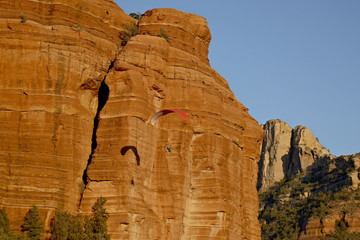 A paraglider flies past a red rock formation, Coconino National Forest, Arizona, United States of America, North America